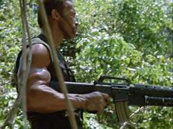 Predator movie Dutch walking cautiously with the butt of his gun against his enormous bicep