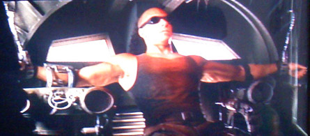 The Chronicles of Riddick, Riddick cuffed about Merc ship