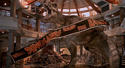 Jurassic Park scene where the t-rex roars in the lobby as the banner reading When Dinosaurs Ruled The Earth falls to his feet